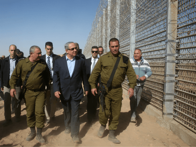 Israeli Prime Minister Benjamin Netanyahu walks with IDF Chief of Staff Gadi Eizenkott, left, as they visit the construction work on the fence between Israel and Jordan Tuesday, Feb. 9, 2016. (Marc Israel Sellem, Jerusalem Post, Pool via AP)