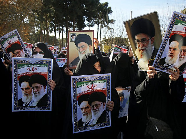 In this photo provided by Tasnim News Agency, women hold posters showing portraits of late Iranian revolutionary founder Ayatollah Khomeini, and Supreme Leader Ayatollah Ali Khamenei during a pro-government rally in the holy city of Qom, Iran, Wednesday, Jan. 3, 2018. Tens of thousands of Iranians took part in pro-government …