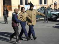 Afghan security personnel escort a man rescued from the Intercontinental Hotel after an attack in Kabul, Afghanistan, Sunday, Jan. 21, 2018. Gunmen stormed the hotel and sett off a 12-hour gun battle with security forces that continued into Sunday morning, as frantic guests tried to escape from fourth and fifth-floor …