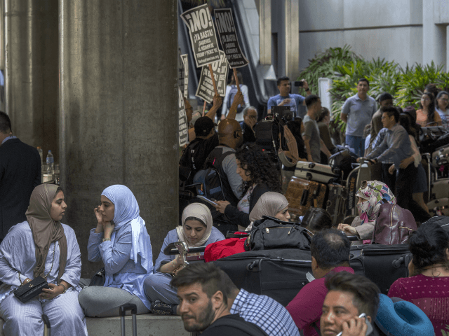 Activists demonstrate as international travelers arrive on the first day of the the partial reinstatement of the Trump travel ban, temporarily barring travelers from six Muslim-majority nations from entering the U.S., at Los Angeles International Airport (LAX) on June 29, 2017 in Los Angeles, California. Under a Supreme Court order, foreigners who do not have a so-called 'bona fide relationship' with a person or entity in the United States can be banned. The ban effects travelers from Iran, Libya, Somalia, Sudan, Syria and Yemen. (Photo by David McNew/Getty Images)