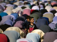 NEW YORK, NY - JUNE 25: A young boy looks on as Muslims participate in a group prayer service during Eid al-Fitr, which marks the end of the Muslim holy month of Ramadan, in Bensonhurst Park in the Brooklyn borough June 25, 2017 in New York City. Muslims around the world are celebrating Eid al-Fitr, which means 'festival of breaking the fast' to mark the end of Ramadan. (Photo by Drew Angerer/Getty Images)