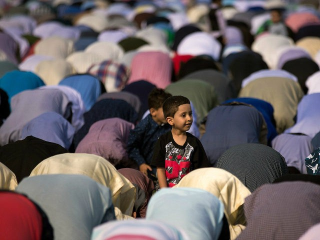 NEW YORK, NY - JUNE 25: A young boy looks on as Muslims participate in a group prayer service during Eid al-Fitr, which marks the end of the Muslim holy month of Ramadan, in Bensonhurst Park in the Brooklyn borough June 25, 2017 in New York City. Muslims around the …