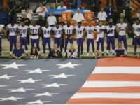 Minnesota Vikings players lock arms during the national anthem before an NFL football game against the Chicago Bears, Monday, Oct. 9, 2017, in Chicago. (AP Photo/Kiichiro Sato)