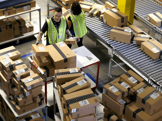 "In this Dec. 2, 2013 file photo, Amazon.com employees organize outbound packages at an Amazon.com Fulfillment Center on ""Cyber Monday"" the busiest online shopping day of the holiday season, in Phoenix. Buying things online could soon get pricier for many people after the U.S. Supreme Court's decision Monday, Dec. 12, …"