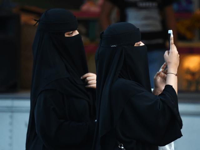 As mulheres caminham pela rua Tahlia na capital saudita Riyadh em 24 de setembro de 2017, durante as comemorações para o aniversário da fundação do reino.  / AFP PHOTO / Fayez Nureldine (O crédito da foto deve ler FAYEZ NURELDINE / AFP / Getty Images)