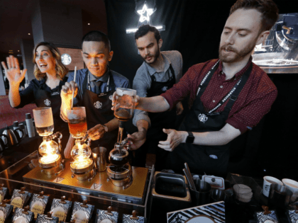 In this Wednesday, March 22, 2017, file photo, baristas from Starbucks' specialized coffee shop, Reserve Roastery, demonstrate a siphon brew of individual cups of coffee before the company's annual shareholder meeting in Seattle. Starbucks is giving its U.S. workers pay raises and stock bonuses in 2018, citing recent tax reform. …