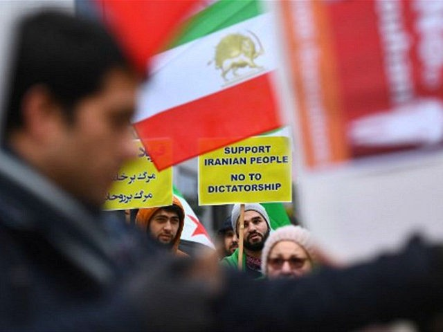 Protesters hold a placard under a flag of the National Council of Resistance of Iran (NCRI) during a demonstration in support of the Iranian people amid a wave of protests spreading throughout Iran, on January 3, 2018, in Brussels. Violent demonstrations have rocked Iran since December 28, 2017, leaving at …