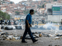 "A man crosses a street blocked with garbage bags during a protest against Maduro in Caracas, on May 2, 2017. Armed ""collectives"" pressure low income urban dwellers from joining the protest movement, forcing them to share the view of the ruling Socialists United Party that the political opposition is orchestrating …"