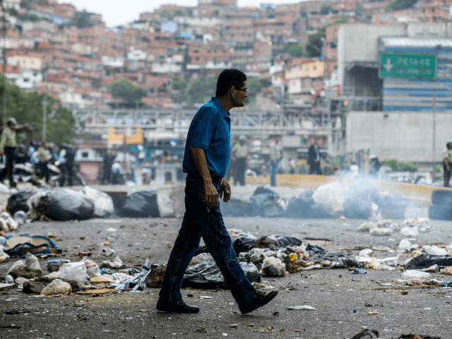 """A man crosses a street blocked with garbage bags during a protest against Maduro in Caracas, on May 2, 2017. Armed """"collectives"""" pressure low income urban dwellers from joining the protest movement, forcing them to share the view of the ruling Socialists United Party that the political opposition is orchestrating a coup against their president. (Photo by FEDERICO PARRA/AFP/Getty Images) [-]"""