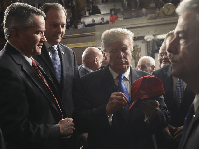 President Donald Trump signs a hat after finishing the State of the Union address in the chamber of the U.S. House of Representatives Tuesday, Jan. 30, 2018, in Washington. (Win McNamee/Pool via AP)
