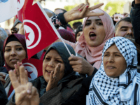 A Tunisian woman holds the national flag and make a sign during a rally to mark seven years since revolution in Tunis, Tunisia, Sunday, Jan. 14, 2018. Tunisian authorities announced plans to boost aid to the needy in a bid to placate protesters whose demonstrations over price hikes degenerated into …