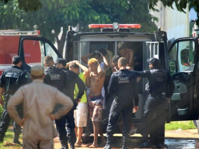 Inmates who escaped during a riot at a Brazilian prison, the Complejo de Aparecida in Goias state, are seen being returned by guards in this photo released by Brazilian newspaper O Popular