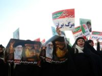 Women hold posters of Iran's supreme leader Ayatollah Ali Khamenei during a pro-regime rally in second city Mashhad on January 4