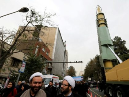 Iranians gather next to a replica of a Ghadr medium-range ballistic missile during a demonstration outside the former US embassy in the Iranian capital Tehran on November 4, 2017
