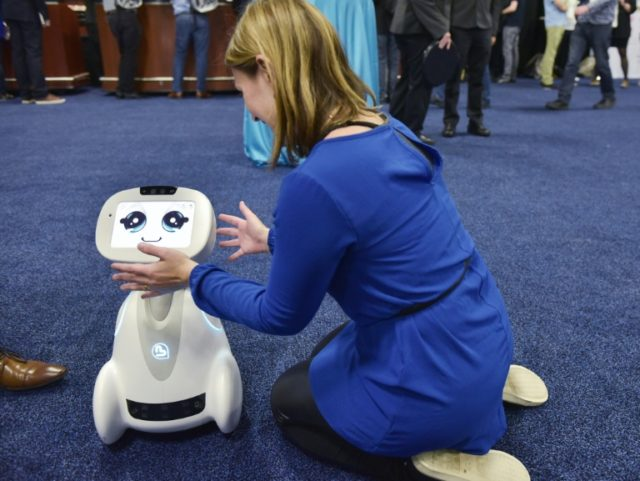 A woman plays with Buddy the companion robot by Blue Frog Robotics during the CES Unveiled preview event in Las Vegas
