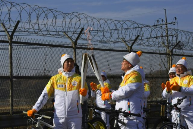 The Olympic flame is passed in front of a military fence on the road leading to the border truce village of Panmunjom during the PyeongChang 2018 Torch Relay in Paju