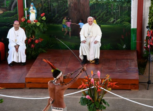 "Pope Francis (C) looks at the performance of an indigenous boy during his visit at ""Hogar Principito"" Children's home, in the Peruvian city of Puerto Maldonado, on January 19, 2018"