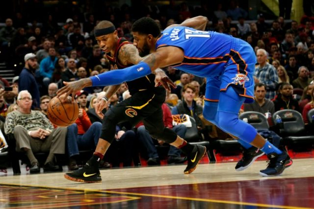 Isaiah Thomas of the Cleveland Cavaliers and Paul George of the Oklahoma City Thunder scramble after a loose ball during the third quarter at Quicken Loans Arena on January 20, 2018 in Cleveland, Ohio