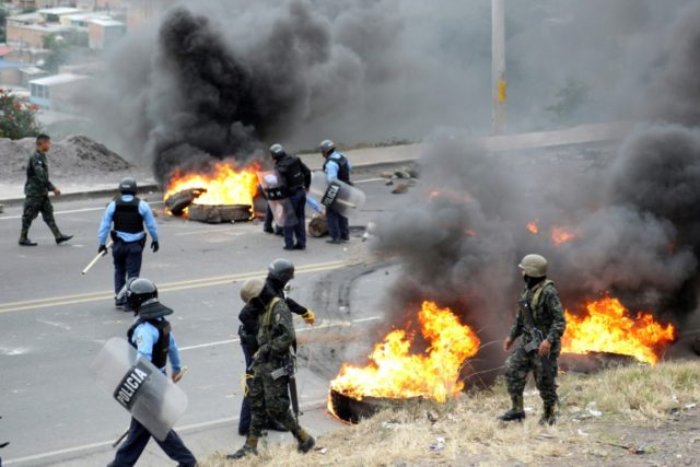 Police and soldiers in the Honduran capital Tegucigalpa try to open up roads blocked by crowds protesting the re-election of president Juan Orlando Hernandez