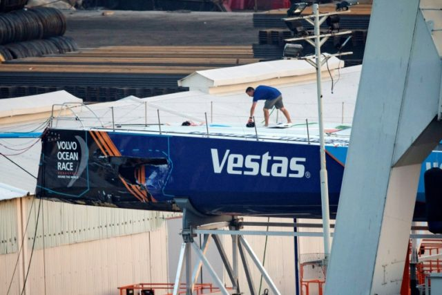 A crew member of the Vestas 11th Hour Racing team walks on their damaged yacht, as it sits in a dock for repairs after a collision with a fishing vessel during the fourth leg of the Volvo Ocean Race, in Hong Kong