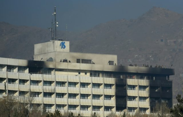 Afghan security personnel take position on the rooftop of the Intercontinental Hotel