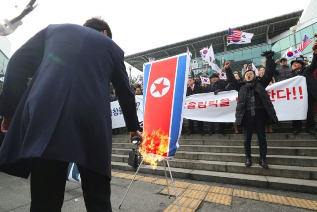 South Korean protestors burn a North Korean flag during an anti-North Korea rally outside Seoul station as a North Korean delegation arrives