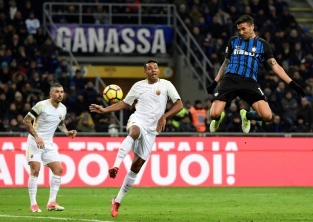 Inter Milan's midfielder Matias Vecino (R) heads the ball to score against Roma at the San Siro stadium in Milan on January 21, 2018