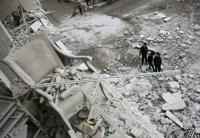 Syrian children look at a building damaged in a missile attack on the besieged rebel-held eastern Ghouta region on the outskirts of Damascus, on January 18, 2018