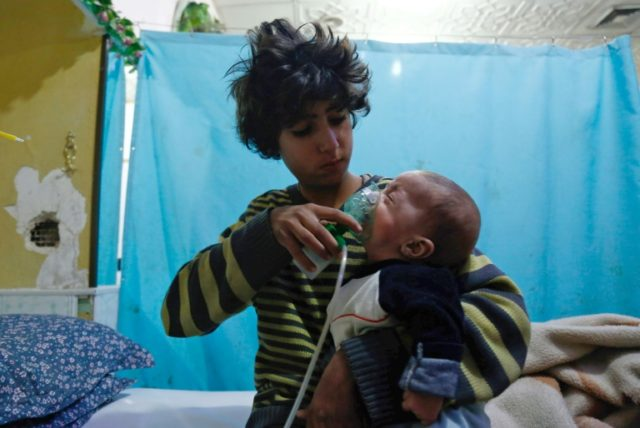 A Syrian boy holds an oxygen mask over the face of an infant at a makeshift hospital following a reported gas attack on the besieged eastern Ghouta region near Damascus on January 22, 2018