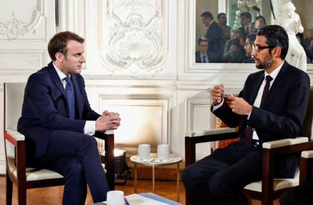 "French President Emmanuel Macron (L) talks with Google CEO Sundar Pichai during the ""Choose France"" summit at the Chateau de Versailles, near Paris, on January 22, 2018"