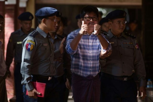 Myanmar police officers escort Reuters journalist Wa Lone as he arrives at the northern district court in Yangon on January 23, 2018