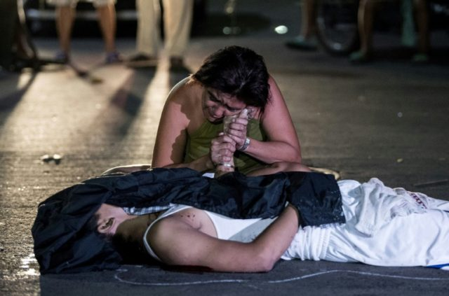 A woman grieves over the body of her son, a victim of the war on drugs
