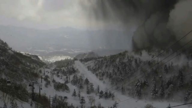 Thick black smoke rolling down the snow-covered side of Japan's Mt. Kusatsu Shirane towards a ski slope after a volcanic eruption