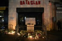 Candles, flowers and messages at a makeshift memorial around the commemorative plaque outside the Bataclan concert hall