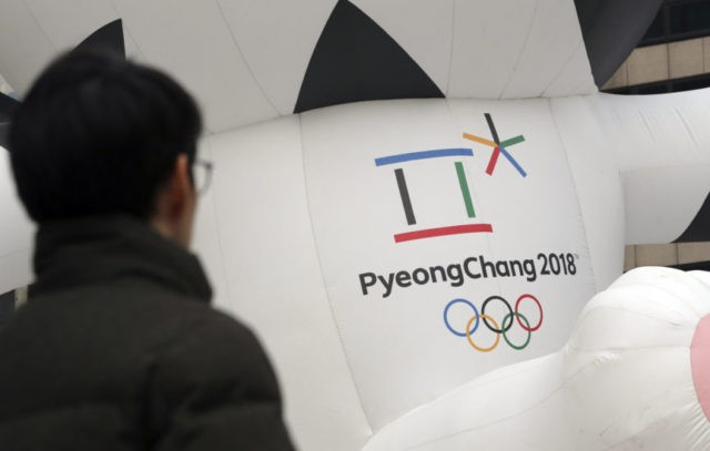 In this Dec. 29, 2017, photo, a man walks by the official emblem of the 2018 Pyeongchang Olympic Winter Games, in downtown Seoul, South Korea. North Korean leader Kim Jong Un said Monday the United States should be aware that his country's nuclear forces are now a reality, not a threat. But he also struck a conciliatory tone in his New Year's address, wishing success for the Winter Olympics set to begin in the South in February and suggesting the North may send a delegation to participate. (AP Photo/Lee Jin-man)