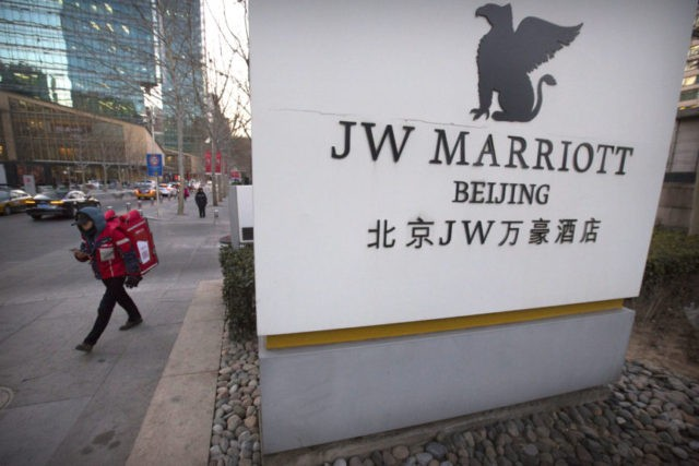 A deliveryman walks away from the entrance of a JW Marriott hotel in Beijing, Thursday, Jan. 11, 2018. The Marriot hotel chain apologized Thursday to China's government for referring to Tibet and self-ruled Taiwan as countries in a customer survey that news reports said Chinese police investigated as a possible crime. (AP Photo/Mark Schiefelbein)