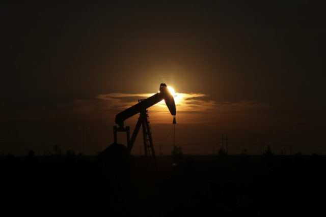 FILE - This June 27, 2017, file photo shows an oil rig at sunset in Midland, Texas. President Donald Trump relentlessly congratulates himself for the healthy state of the U.S. economy, with its steady growth, low unemployment, busier factories and confident consumers. But in the year since Trump's inauguration, most economists tend to agree on this: The economy has essentially been the same sturdy one that he inherited from Barack Obama. (Steve Gonzales/Houston Chronicle via AP, File)