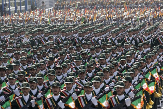 In this Sept. 21, 2012 photo, Iran's Revolutionary Guard troops march during a military parade commemorating the anniversary of start of the 1980-88 Iraq-Iran war, in front of the shrine of the late revolutionary founder Ayatollah Khomeini, just outside Tehran, Iran. Supreme Leader Ayatollah Ali Khamenei has ordered the Revolutionary Guard to loosen its hold on the economy, the country's defense minister says, raising the possibility that the paramilitary organization might privatize some of its vast holdings. (AP Photo/Vahid Salemi, File)