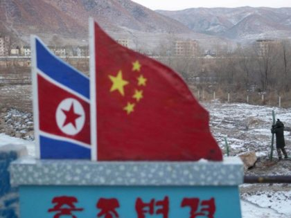"""In this Dec. 8, 2012, file photo, Chinese paramilitary policemen build a fence near a concrete marker depicting the North Korean and Chinese national flags with the words """"China North Korea Border"""" at a crossing in the Chinese border town of Tumen in eastern China's Jilin province. A U.S. Treasury …"""