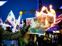 PYEONGCHANG, SOUTH KOREA - FEBRUARY 9, 2018: People burn a portrait of Kim Jong-un in protest against North Korean athletes' participation in the 2018 Winter Olympic Games outside the Pyeongchang Olympic Stadium ahead of the opening ceremony in Pyeongchang, South Korea. Sergei Bobylev/TASS (Photo by Sergei Bobylev\TASS via Getty Images)