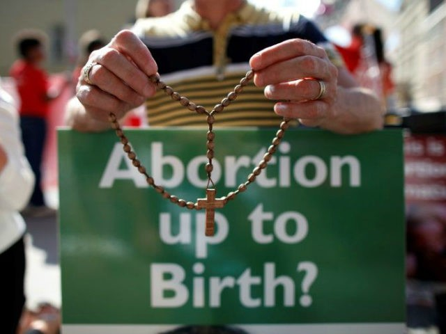 """Abortion up to Birth?"" sign by someone holding a cross"