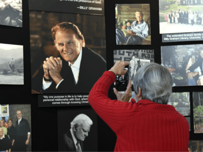 Lyn Warwick of Black Mountain, N.C., photographs a memorial display of Rev. Billy Graham inside Chatlos Chapel at the Billy Graham Training Center at the Cove on Wednesday, February 21, 2018 in Asheville, NC. Warwick is friends with Gigi Graham, Billy Graham's daughter. (AP Photo/Kathy Kmonicek)
