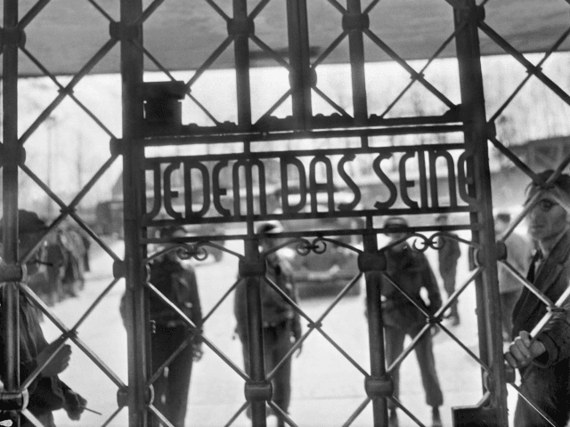 Prisoners and US army soldiers stand behind the gate of Buchenwald concentration camp on which it is written 'Jedem das seine' (To each his just deserts). The construction of Buchenwald camp started 15 July 1937 and was liberated by US General Patton's army 11 April 1945. Between 239,000 and 250,000 …
