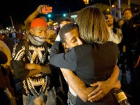 State Sen. Catherine E. Pugh, right, D-Baltimore, embraces a protestor while urging the crowd to disperse ahead of a 10 p.m. curfew in the wake of Monday's riots following the funeral for Freddie Gray, Tuesday, April 28, 2015, in Baltimore. (AP Photo/David Goldman)