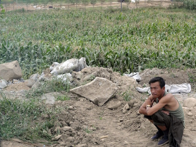 A farmer rests beside his field in the outskirts of Rason city in North Korea on August 29, 2011. Keen to boost tourism and earn much-needed cash, authorities in the impoverished nation have decided to launch a cruise tour from the rundown northeastern port city of Rajin to the scenic …
