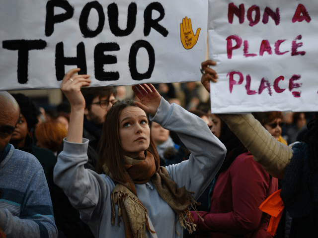 Protesters hold banners during a demonstration against police brutality on February 18, 2017 on the place de la Republique in Paris, following the alleged rape of a black youth, identified only as Theo, with a police baton, an incident that has sparked 10 nights of rioting and more than 200 …