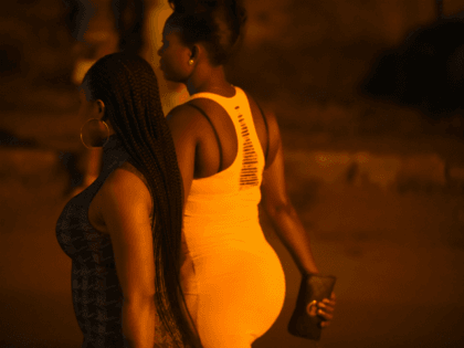 Prostitutes stand walk on the street in Benin City, capital of Edo State, southern Nigeria, on March 29, 2017. In Benin City, Nigeria's capital of illegal migration, no one says the word 'prostitution'. The word on the street for the young girls who leave for Italy or France is 'hustling'. …