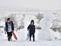 BELFAST, NORTHERN IRELAND - DECEMBER 08: Children off from school due to the weather make their way past a large snowman on Black mountain on December 8, 2017 in Belfast, Northern Ireland. The MET Office has issued a weather warning across the UK for heavy snow with northern and western parts bearing the brunt of the cold snap. (Photo by Charles McQuillan/Getty Images)