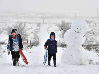 BELFAST, NORTHERN IRELAND - DECEMBER 08: Children off from school due to the weather make their way past a large snowman on Black mountain on December 8, 2017 in Belfast, Northern Ireland. The MET Office has issued a weather warning across the UK for heavy snow with northern and western …