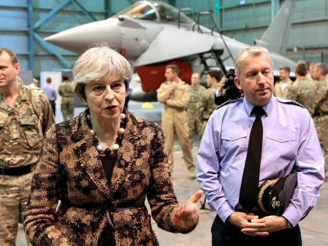 British Prime Minister Theresa May (L) speaks with troops upon her arrival to wish British servicemen happy holidays, at the RAF Akrotiri British military base, in the British Overseas Territory, on the east Mediterranean island of Cyprus on December 21, 2017. / AFP PHOTO / POOL / Petros Karadjias (Photo …